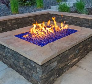 Natural stone square fire pit with purple glass beads in the flame