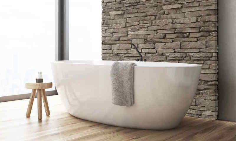 A stone veneer accent wall helps transform this bath into a spa.