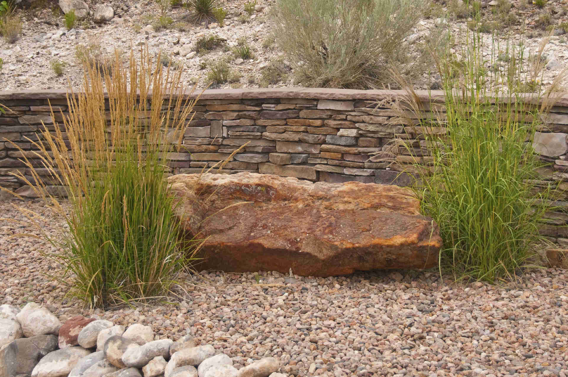 Landscape boulder with tallgrass, a stone retaining wall and decorative gravel