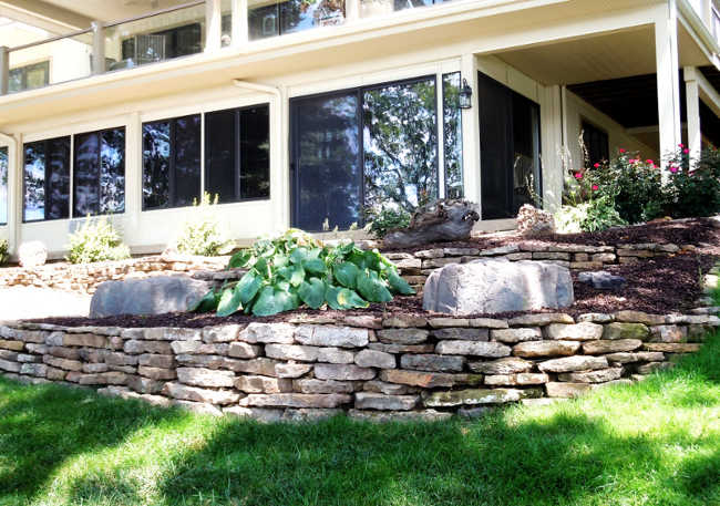 Dry stack natural stone retaining walls used as planters in front of a lake home