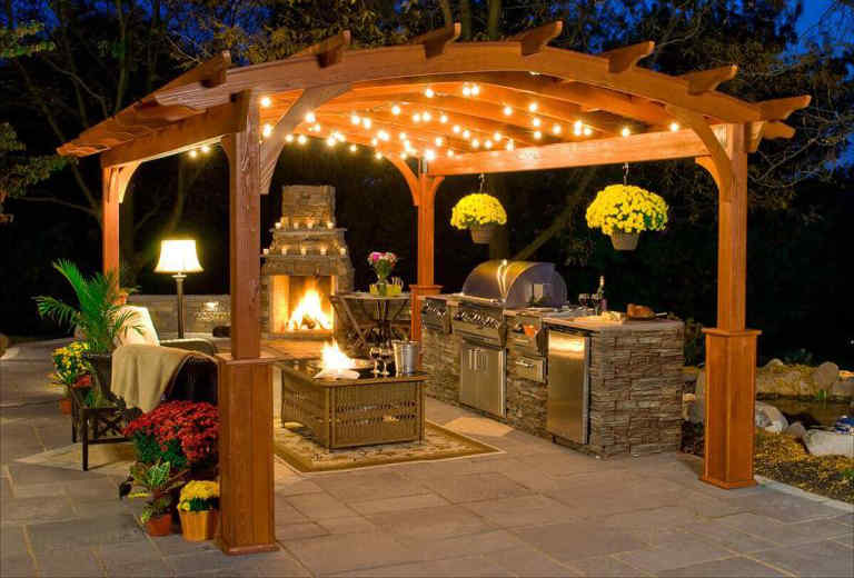 A beautiful outdoor kitchen lit up on a covered patio at night.