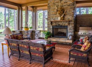 Outdoor stone fireplace in an outdoor living room with comfortable furniture