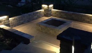 Beautiful fire pit and landscape lit up with low voltage lighting.