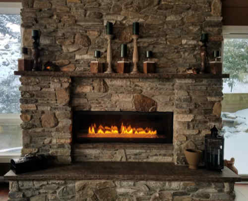 A rustic setting of a large stone fireplace with mantle and hearth lit with burning flames.