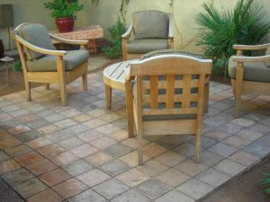 Outdoor patio furniture arranged in an outdoor space built with multi-colored pavers.