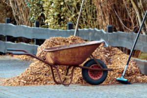 A wheelbarrow beside a pile of bulk cedar mulch
