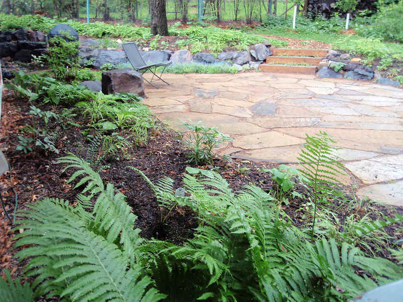 Patio made of Flagstone pavers set in wooded area with mulch and greenery landscaping