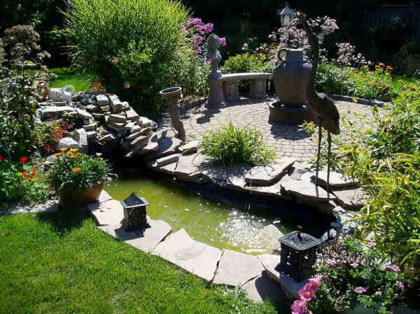 Beautiful backyard pond feature with natural stone landscaping