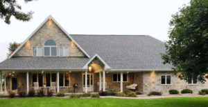 Large two-story home with natural thin stone veneer and large porch
