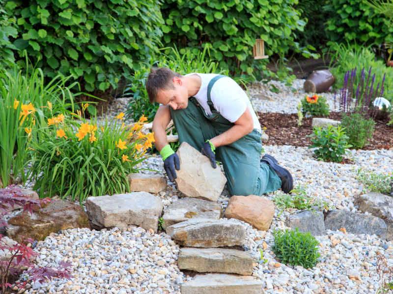 Landscaper placing rock in landscaping project at Lake of the Ozarks