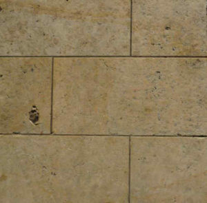 Earth tone limestone floor tile showing the porous nature of the stone