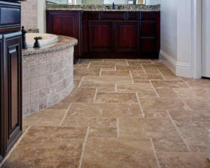 Bathroom with travertine floor tile contrasted by cherry wood Vanity base