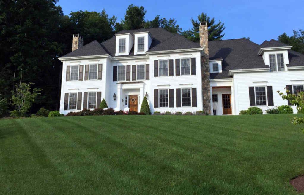 Large dark green lawn in front of a nice white home