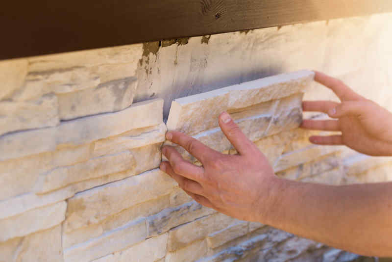 Person's hands installing natural thin stone veneer tile on an exterior wall
