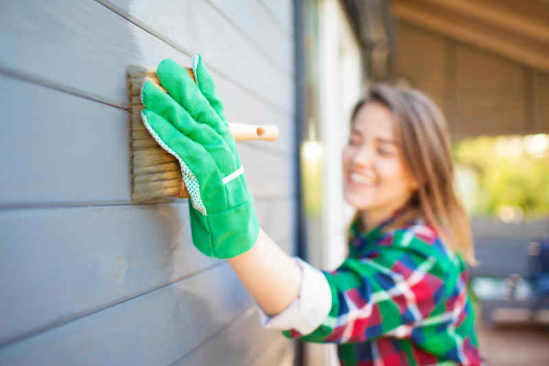 Woman wearing rubber glove and painting her house