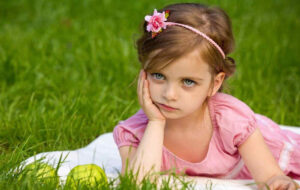 Little girl sitting grass looking unhappy