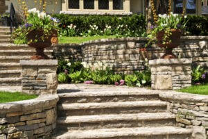 Natural stone steps, posts, landscaping and retaining wall in front of a house