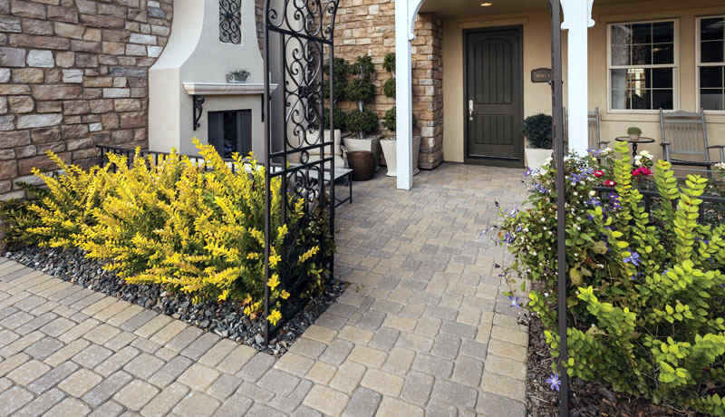Concrete pavers in a patio and entryway with white columns and nice shrubbery