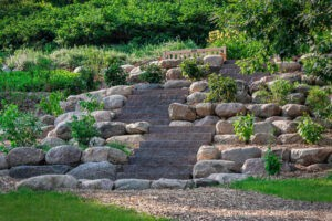 Stone steps built into a backyard with boulders and landscape rocks accenting the design.