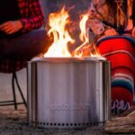 Solo Stove portable fire pit with a strong flame burning set between two campers