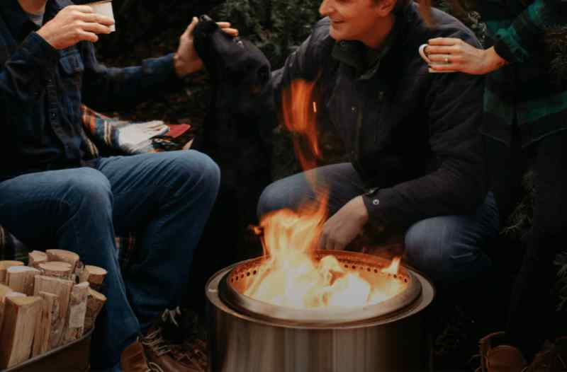 A Solo Stove smokeless fire pit being shared by friends around a campfire
