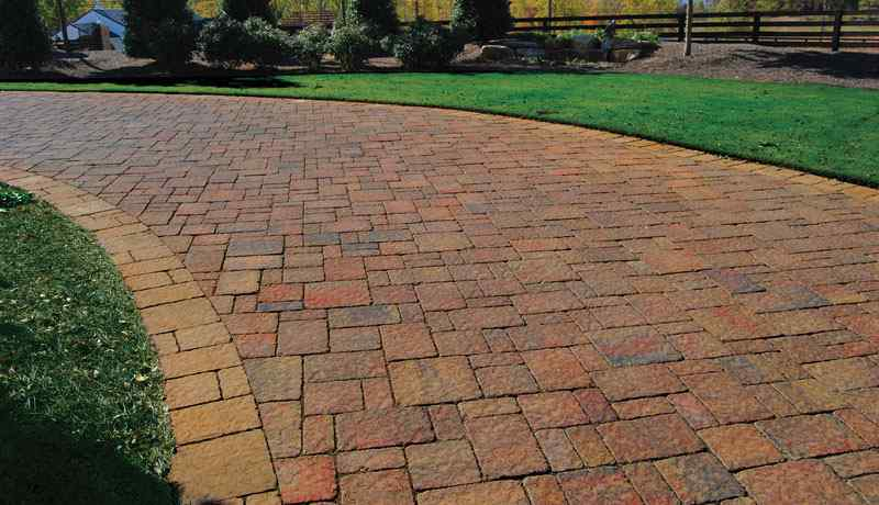 Driveway paved with multicolored pavers, with green grass on either side