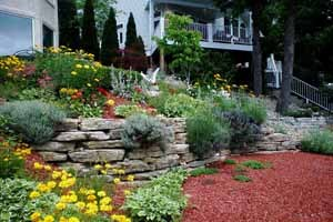 A stone ledge rock raised flower bed with red cedar mulch and flowers