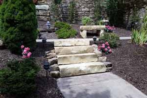 Stone steps surrounded by mulch, with a stone bench in the background