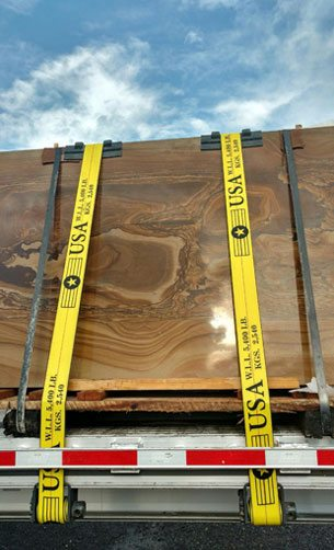 Large cinnamon swirl landscaping stone slab delivery strapped to a truck